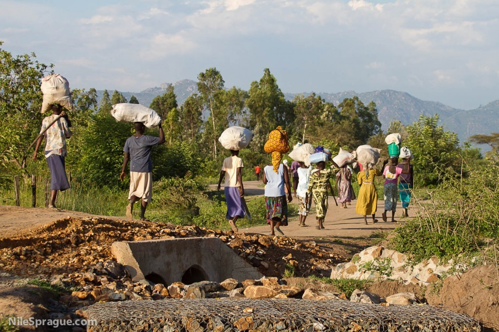 Women carrying sacks on their heads after market, Kisumu, Kenya.
